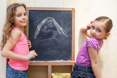Two little girls draw with chalk on blackboard Royalty Free Stock Photography