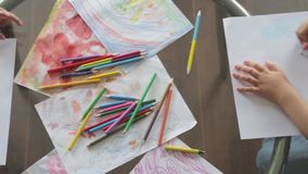 Two little girls draw with crayons sitting at table. top view stock video footage