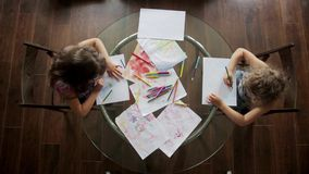 Two little girls draw with crayons sitting at table. top view. Two little girls draw with crayons sitting at table stock footage