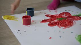 Two little girls draw with finger paints. Two little girls draw with finger stock footage