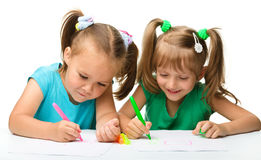 Two little girls draw with markers stock image