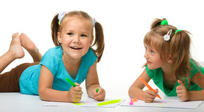 Two little girls draw with markers stock photo