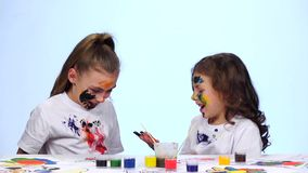 Two little girls draw their palms on the shirt. White background. Slow motion. Two little girls play and have their palms in paint, the girl touches her sister`s stock video footage