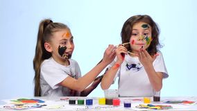 Two little girls draw their palms on the shirt. White background. Slow motion. Two little girls play and have their palms in paint, the girl touches her sister`s stock video