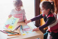 Two little girls drawing a colorful pictures using pencil crayon. Two little girls drawing a colorful pictures of house and playing children using pencil crayons Royalty Free Stock Photo