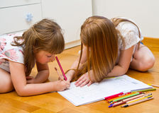 Two little girls drawing on the floor Stock Images