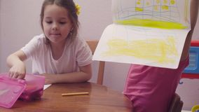 Two little girls drawing at a table. 4K stock video footage