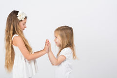 Two little girls dressed in white playing stock images