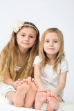 Two little girls dressed in white sitting Stock Photography