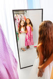 Two little girls with dresses in the mirror Stock Images