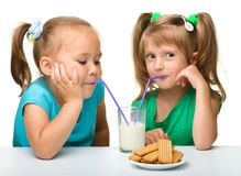 Two little girls are drinking milk. From one glass using straw, isolated over white Royalty Free Stock Photography
