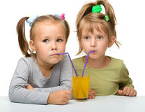 Two little girls are drinking orange juice Royalty Free Stock Photography