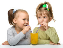 Two little girls are drinking orange juice. From one glass using straw, isolated over white Stock Image
