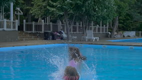 Two little girls dropping into swimming pool at aquapark. Summer holiday.  stock footage