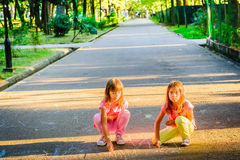 Two little girls drowing with chalk in the park. Two little girls are drowing with chalk in the park Stock Images