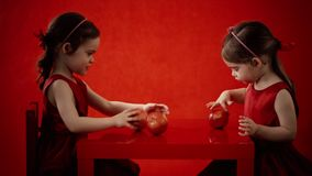 Two little girls eat apples on a red table stock footage