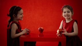 Two little girls eat apples on a red table stock video footage