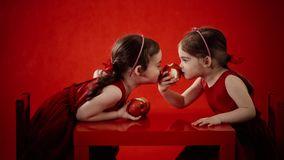 Two little girls eat apples on a red table stock video