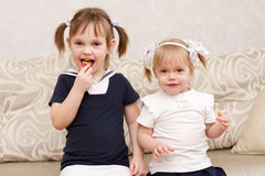 Two little girls eat candies Stock Photography