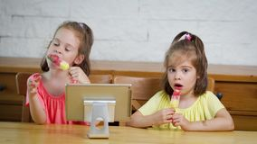 Two little girls eat ice cream and watch the cartoon on the tablet. Two little girls eat a delicious colorful ice cream and watch the cartoon on the tablet at stock footage