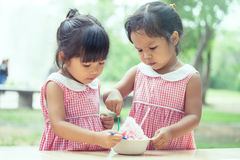 Two little girls eat ice cream together Royalty Free Stock Photos