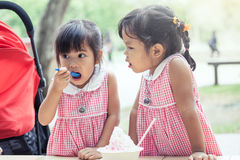 Two little girls eat ice cream together. In vintage color tone Royalty Free Stock Photos