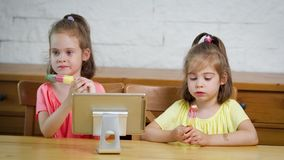 Two little girls eat ice cream and watch the cartoon on the tablet. Two little girls eat a delicious colorful ice cream and watch the cartoon on the tablet at stock video