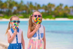 Two little girls eating bright lollipops on the Royalty Free Stock Image