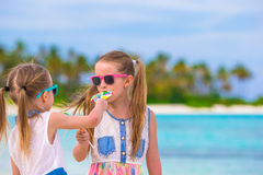 Two little girls eating bright lollipops on the Royalty Free Stock Images