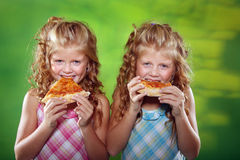 Two little girls eating pizza. Beautiful twin sisters eating pizza on the green background Stock Photos