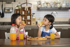 Two Little Girls Eating Pizza Royalty Free Stock Photo