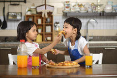 Two Little Girls Eating Pizza Royalty Free Stock Image