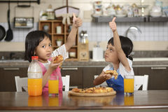 Two Little Girls Eating Pizza Royalty Free Stock Photos