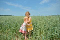 Two little girls embracing in a field Royalty Free Stock Photography