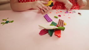 Two little girls are engaged in molding plasticine at the table. Hands of children close-up. Two little girls are engaged in molding plasticine at the table stock footage