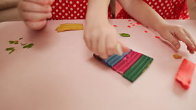 Two little girls are engaged in molding plasticine at the table. Hands of children close-up. Two little girls are engaged in molding plasticine at the table stock video footage