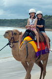 Camel ride. Two little girls enjoying a camel ride on the beach Stock Photo