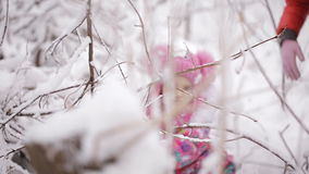Two little girls are entangled in the snowy forest. Two little sisters wandering in the winter woods stock video
