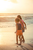 Two little girls explore the beach at sunset Stock Image