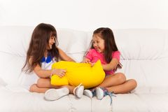 Two little girls fighting over pillow Royalty Free Stock Images