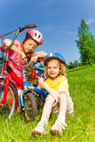 Two little girls fixing bicycles Royalty Free Stock Images