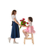 Two little girls with flowers. Lovely girl in beautiful blue skirt giving bouquet of red flowers to her smaller sister. Two lovely sisters in holiday dresses Stock Photos
