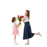 Two little girls with flowers. Small girl in beautiful pink dress giving bouquet of red flowers to her sister. Two lovely sisters in holiday dresses isolated Royalty Free Stock Photography