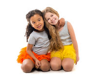 Two little girls-friends with different complexion sitting on the floor. Two little smiling girls-friends with different complexion sitting on the floor  on Stock Images