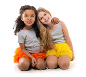 Two little girls-friends with different complexion. Two little smiling girls-friends with different complexion sitting on the floor isolated on white background Royalty Free Stock Photo
