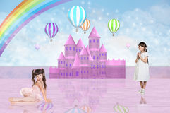Two little girls in front of a pink fairy castle Royalty Free Stock Image