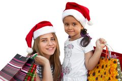 Two little girls in fur-cap with shopping bags. Christmas. Two little girls in fur-cap with shopping bags. Isolated over white background. Christmas Stock Photo