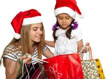 Two little girls in fur-cap with shopping bags. Christmas. Two little girls in fur-cap with shopping bags. Isolated over white background. Christmas Royalty Free Stock Photography