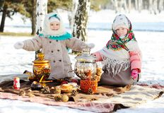 Two little girls in fur coats and shawls in Russian style on his stock image