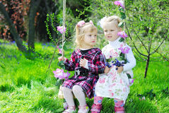 Two little girls girlfriend on a swing Stock Photos